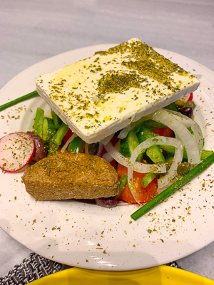 Large piece of feta cheese served on a greek salad