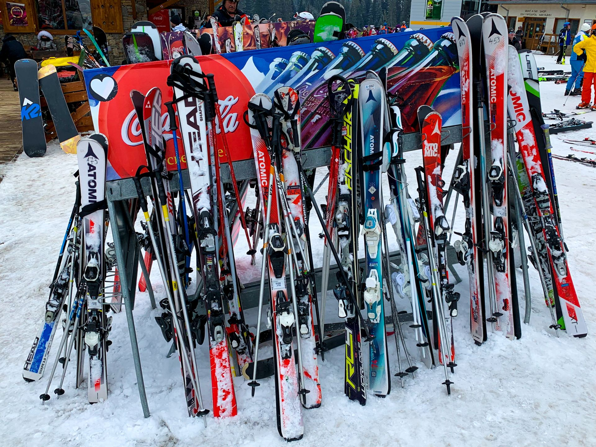 Numerous skis stood up in the racks on the ski slopes